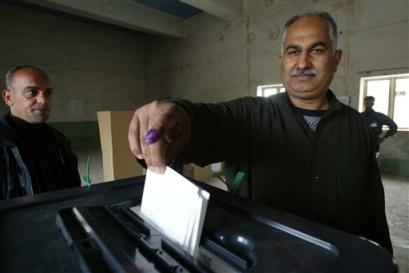 Iraqi man with inked finger drops his ballot